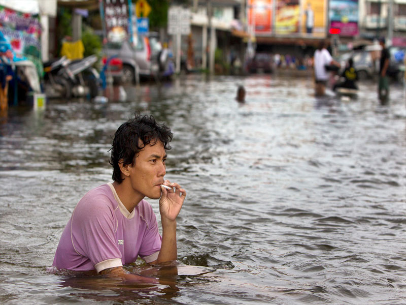 man-smokes-cigarette-flooded-street-ayutthaya-floods